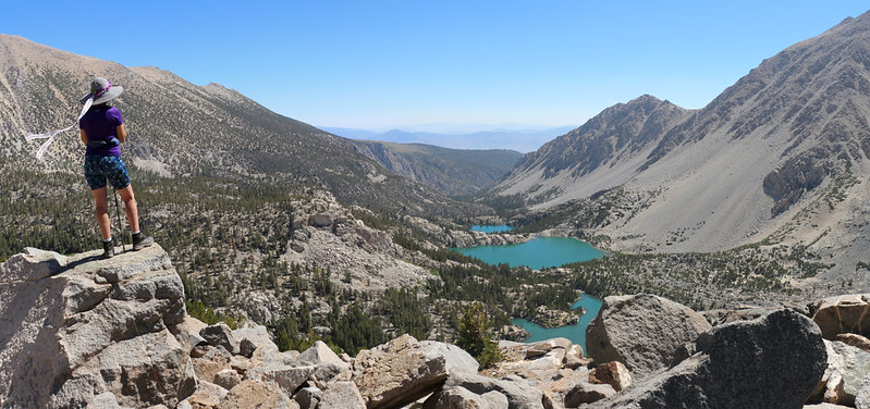 Panorama view of Vicki on a boulder looking down at the Big Pine Lakes Basin from the Palisade Glacier Trail