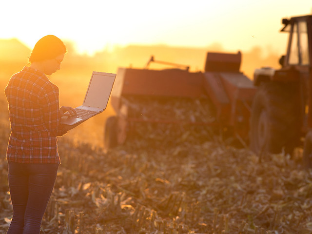A farmer using a laptop in front of farm equipment