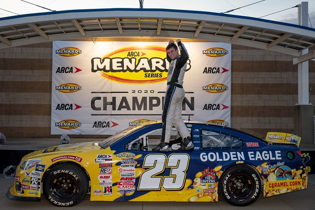 Bret Holmes standing on his race car in Victory Lane.