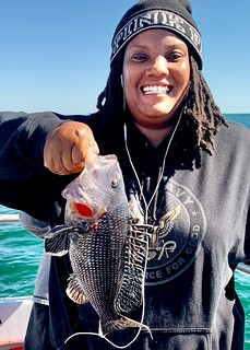 Photo of woman with her catch of a black sea bass