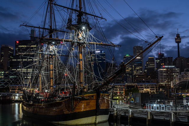 Dawn clouds over Sydney's Darling Harbour with a replica of Cook's Endeavour moored at the Maritime Museum.