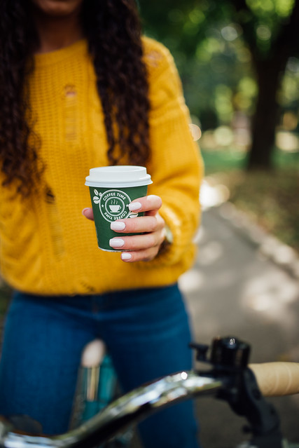 Woman in yellow sweater holding a green cup of coffee while sitting on a bike.