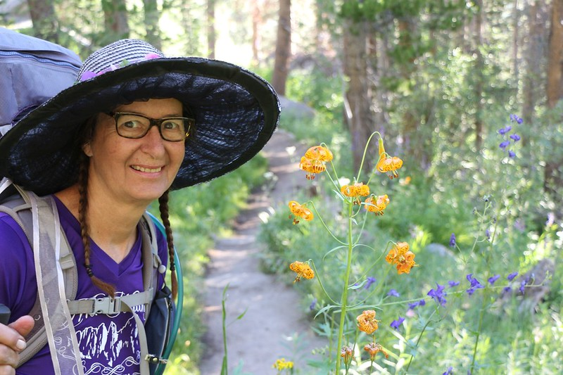 Happy Vicki posing next to some Tiger Lilies on the NF Big Pine Creek Trail