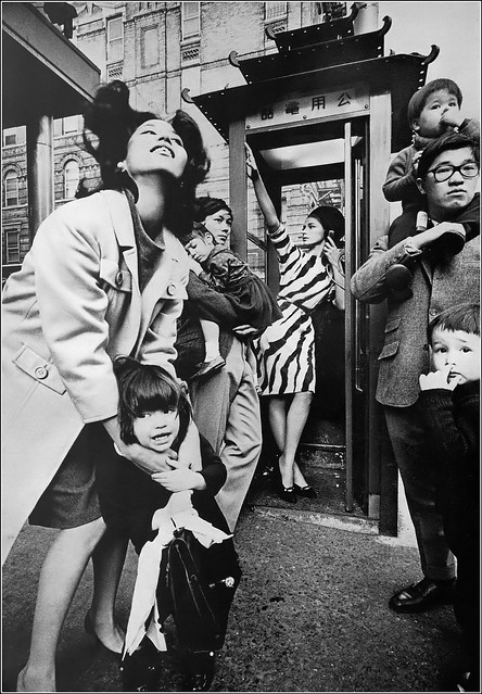 Fashion by L'Aiglon, from left: China Machado, fashion photographer James Moore, unidentified model and fashion photographer Hiro, photo by Jeanloup Sieff in China Town, New York City,  Harper's Bazaar, July 1964