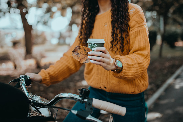 Woman with curly hair holding a cup of coffee and a leaf in her hand while sitting on a bike.