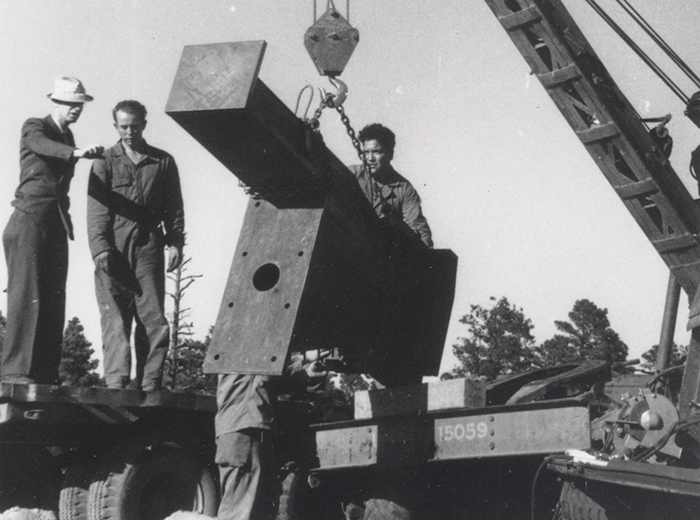 Several men observe the installation of the x-ray detector post at P-Site.