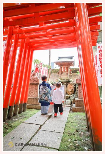 七五三 神社の赤い鳥居をくぐる兄弟の写真