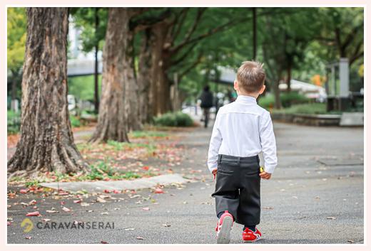 並木道を歩く小さな男の子の後ろ姿