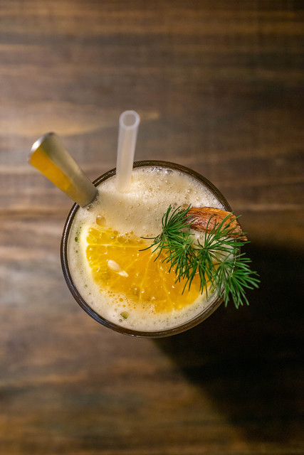 Top View Photo of Iced Orange-Cinnamon Tea with Slice of Orange, Rosemary, Spoon and Straw in a Cocktail Glass