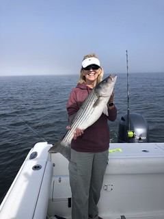 Photo of a woman on a boat holding a large striped bass