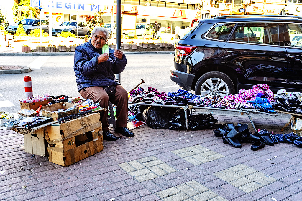 Man selling slippers, shoe polish, razors and combs, etc on sidewalk on 10-23-20--Shtip