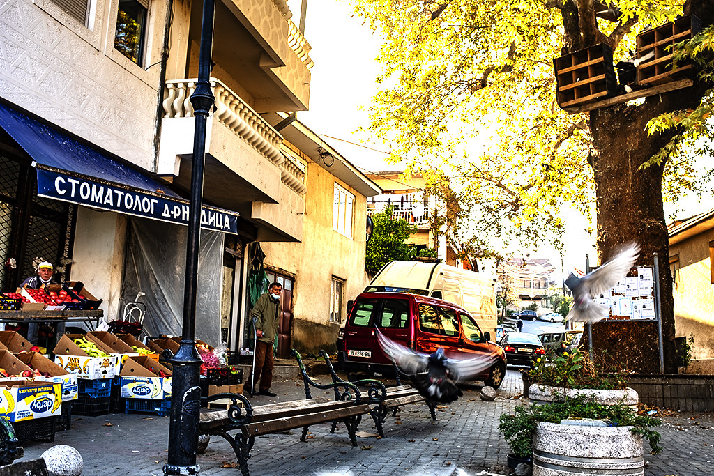 Broken benches, death notices and pigeons at small square--Veles