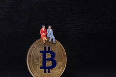 Older couple sitting on a golden Bitcoin