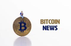 Man sitting on Bitcoin coin with Bitcoin News text