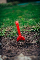Red toy spatula in the ground.