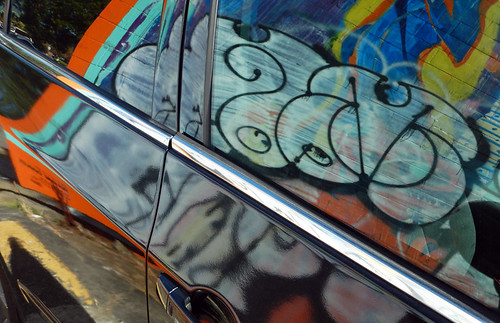 bright graffiti reflected on a shiny car on my Main St. mural walk