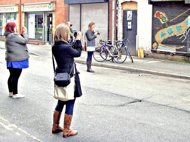 Women taking photos of street art in Manchester