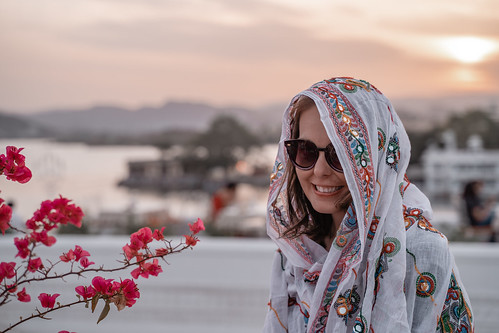 smile flowers cute scarf lake rajasthan cold headscarf caucasian 30s warmingup pichola sunglasses woman chilly udaipur pink sunset tourism happy india