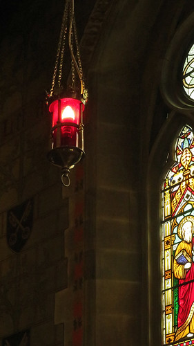 Red hanging lantern and stained-glass windows in Northup's tiny perfect church in Wales