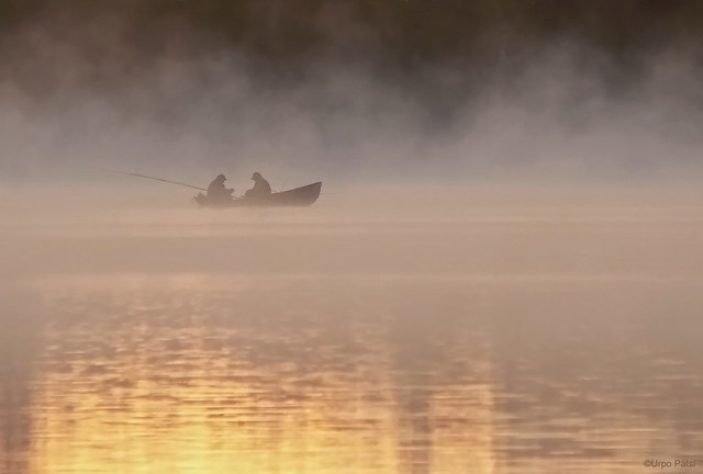 Two friends fishing on a misty lake