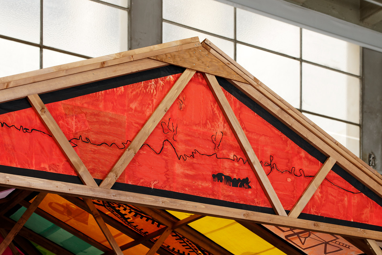 a detail of the front triangular roof panel. It's red with a black outline running horizontally, suggesting a burning horizon with mangrove roots or an animal herd in the foreground
