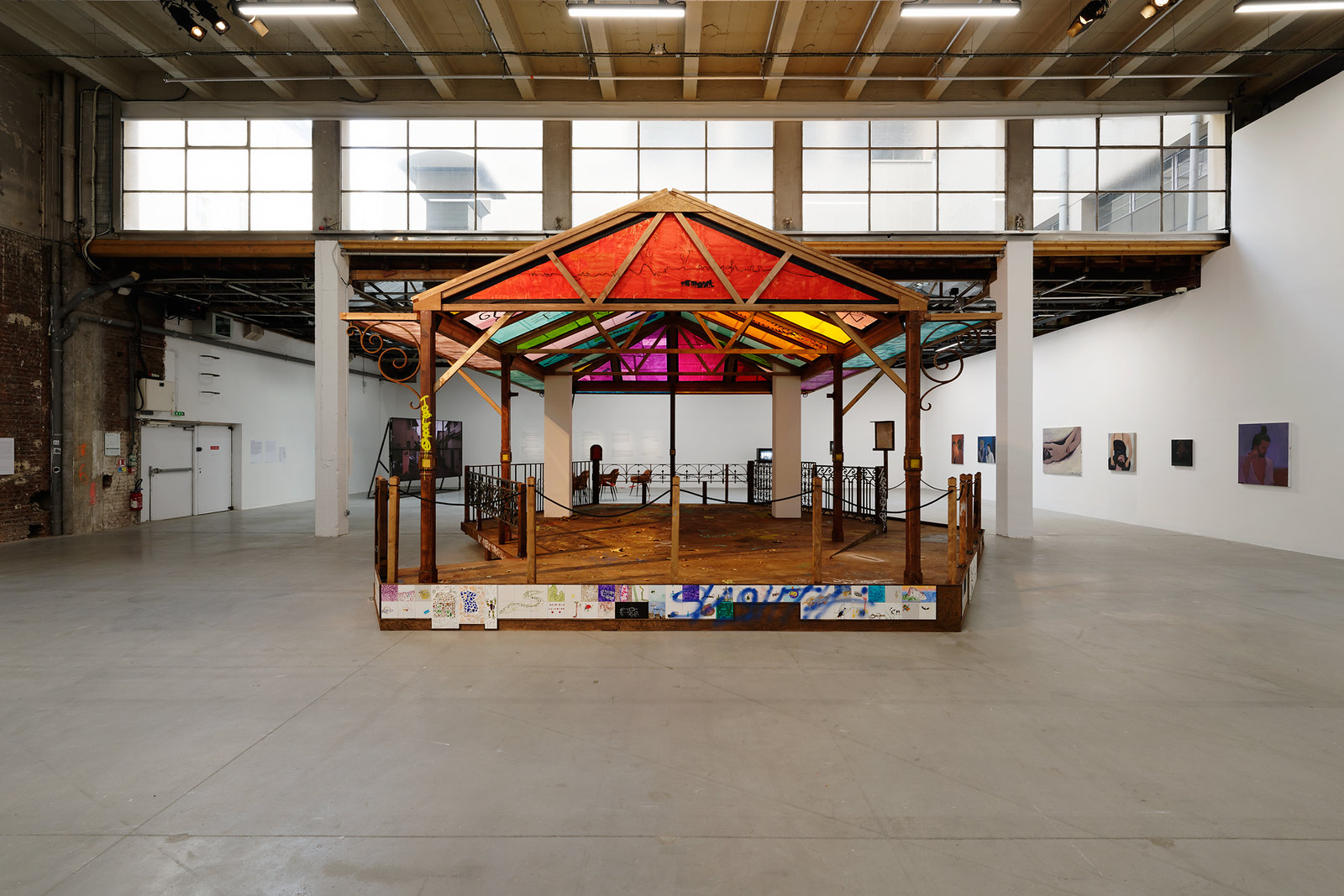 a wooden kiosk or bandstand in a larger room. The kiosk is hexagon shaped and has colourful roof panels. There is decorative wrought iron around the half the perimeter of the kiosk and hip-height poles with rope strung between them around the other half of the perimeter