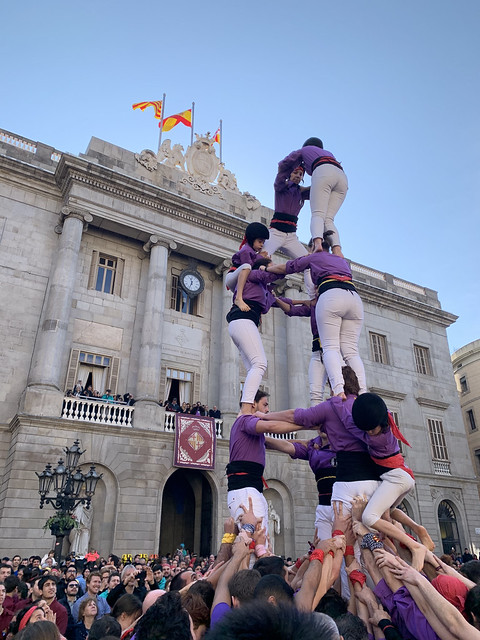 People wearing purple shirts, white pants and yellow helmets make a human tower four people tall in front of an old stone building.