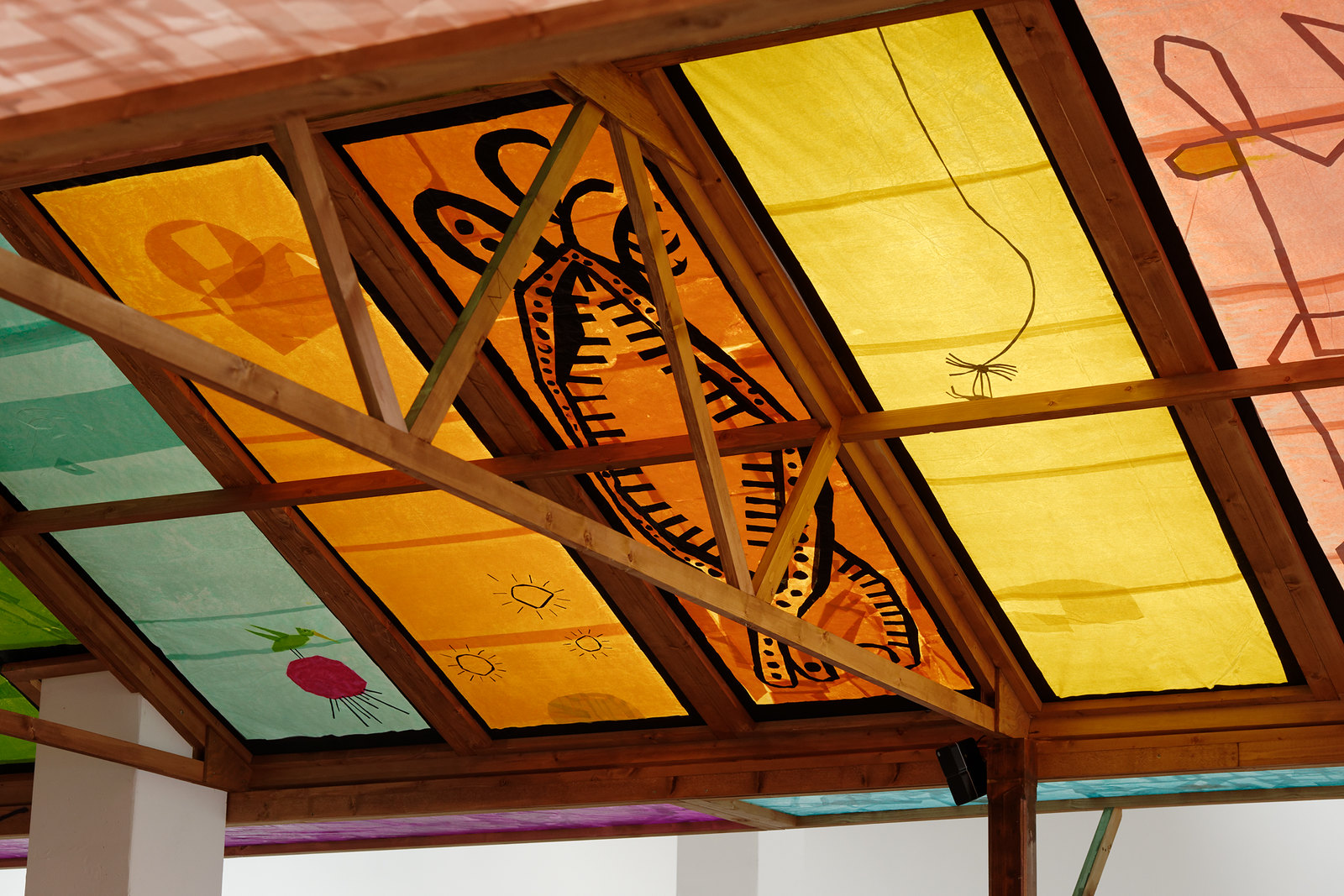 a view of some of the roof panels from inside the kiosk. One seems to be a vagina dentata with various small suns and moons circling the mouth. On the panel adjacent to this a spider has caught its prey. To the left of the vagina dentata are three delicate suns, and then to the left of this a bird with a long beak and wings rasied stands upon a pink planet floating in a blue space.