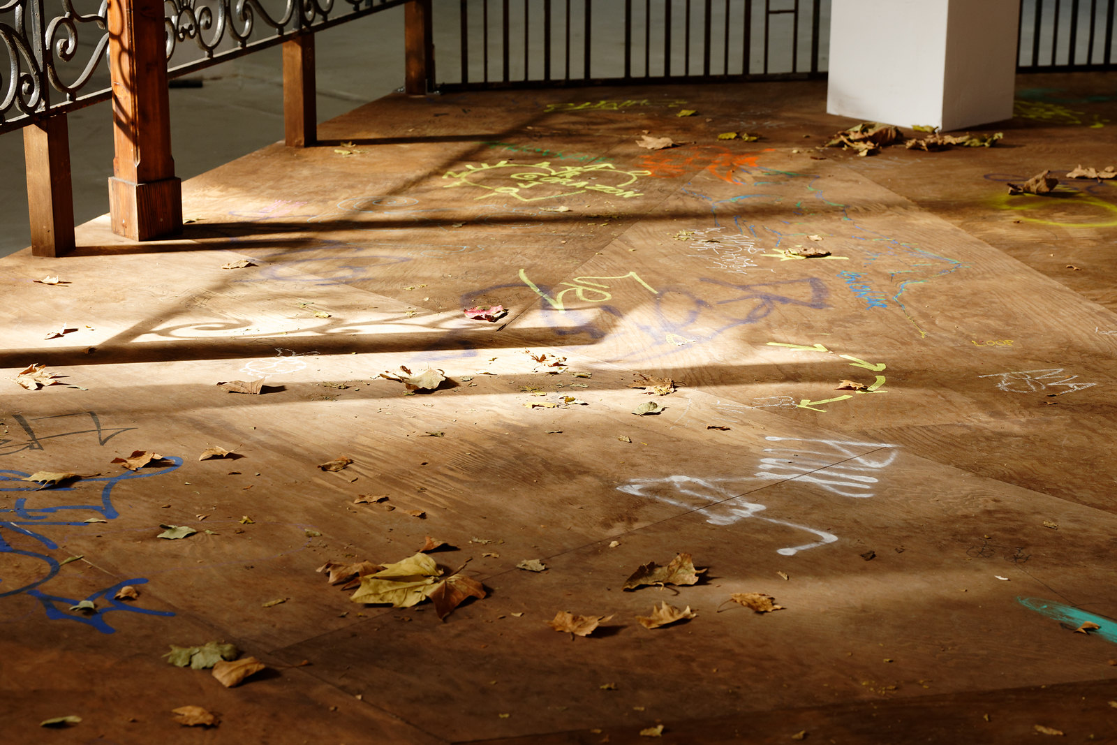 The floor of the kiosk which is strewn with autumn leaves and graffiti