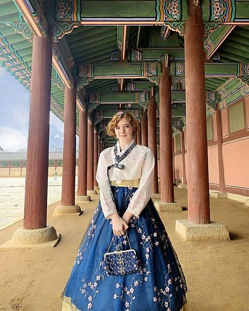 A female student poses in the courtyard of a Korean temple wearing a hanbok with a white jacket and blue skirt embroidered with delicate flowers.