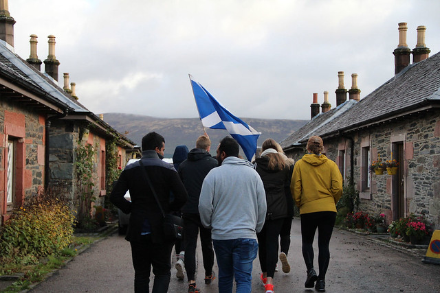A group of students bundled in jackets carry a blue and white Scottish flag as they walk away from the camera along a narrow road lined with old stone cottages.