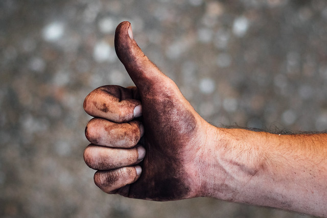 Manual worker's dirty hand showing a thumbs up