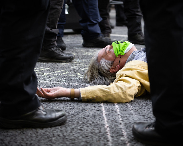 A protester refuses police orders to cease blocking road