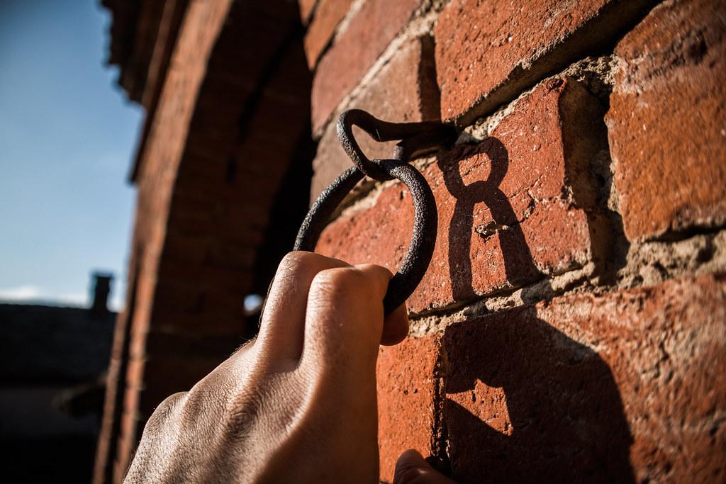 Man pulling an iron loop hanging from a barn brick wall