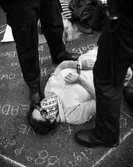 An arrested protester lies at the feet of police officers