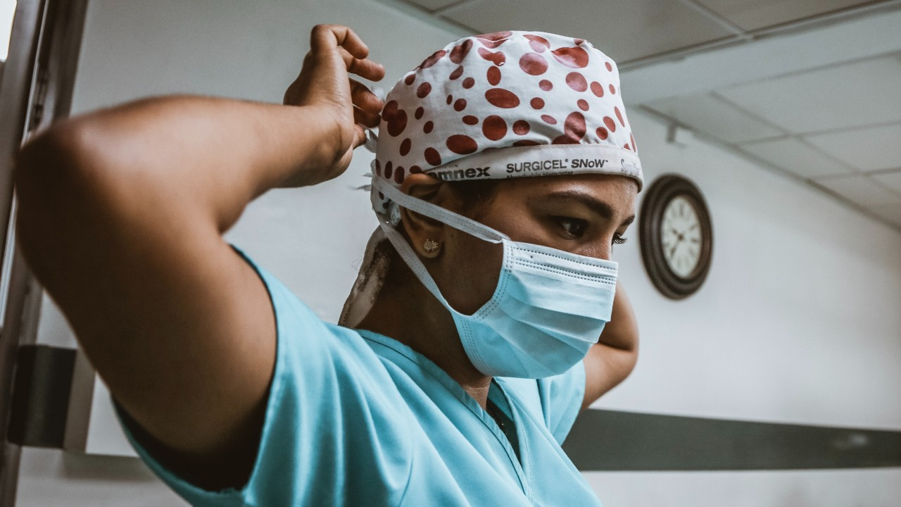 A doctor in a scrub cap tying a face mask