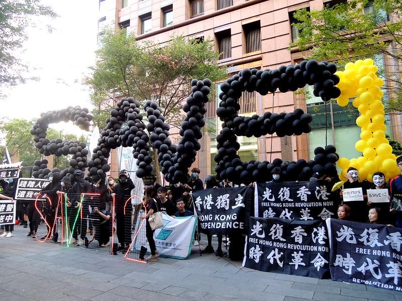 工作人員在遊行中途的短暫休息中高舉SAVE12的氣球標語。圖/永社協會提供。