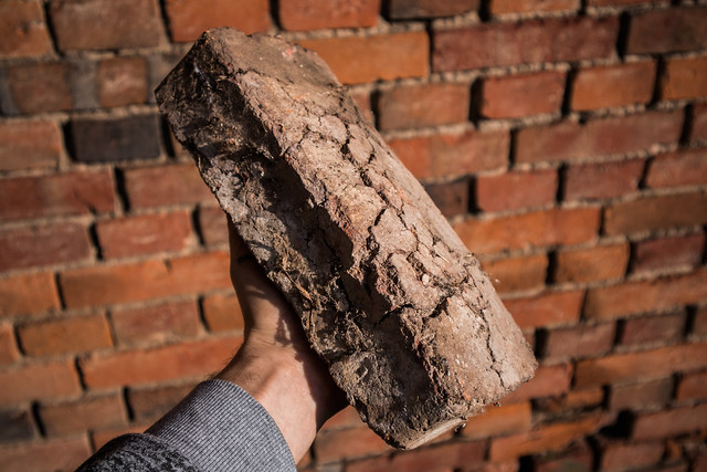 Man holding a bloated and cracked brick unusable for construction work