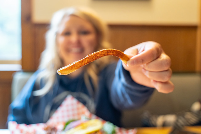 Hungry blonde woman holds up a single sweet potato french fry while eating in a restaurant. Woman is intentionally blurred, focus on the fries