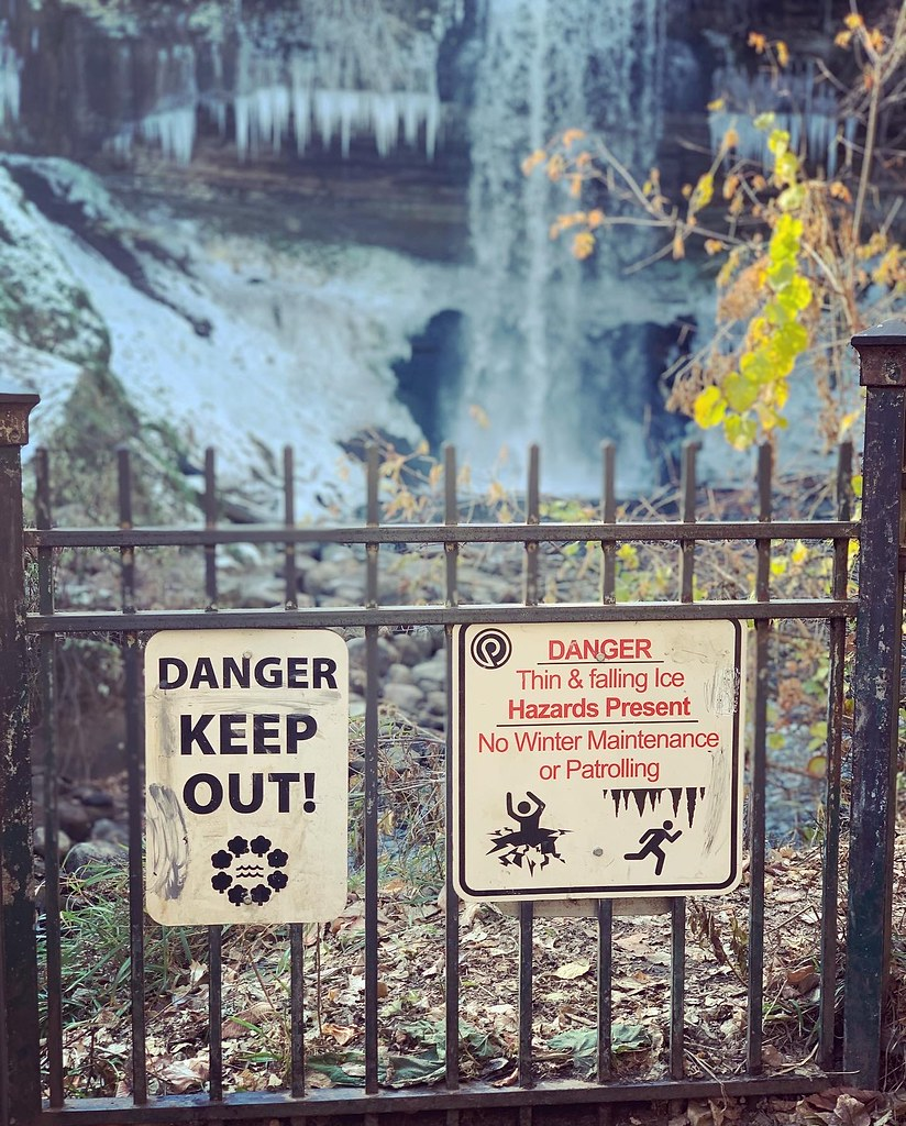 DANGER signs on the fence in front of the frosty Minnehaha Falls