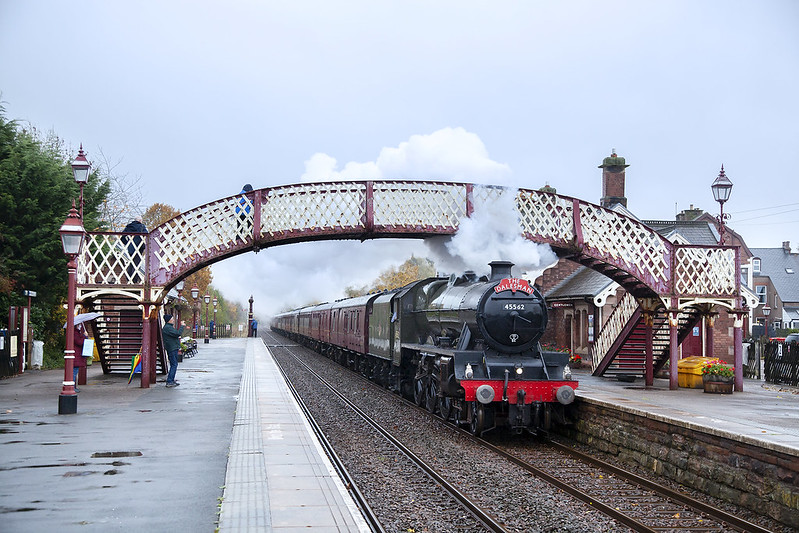 Framed by the original footbridge, Jubilee No.45699 'Galatea' running as No.45562 'Alberta' races through Appleby non stop with the northbound Pendle Dalesman on a drizzly day in late October. This tour would later take the Upperby Curve to avoid Carlisle Station and return south via the West Coast Mainline.