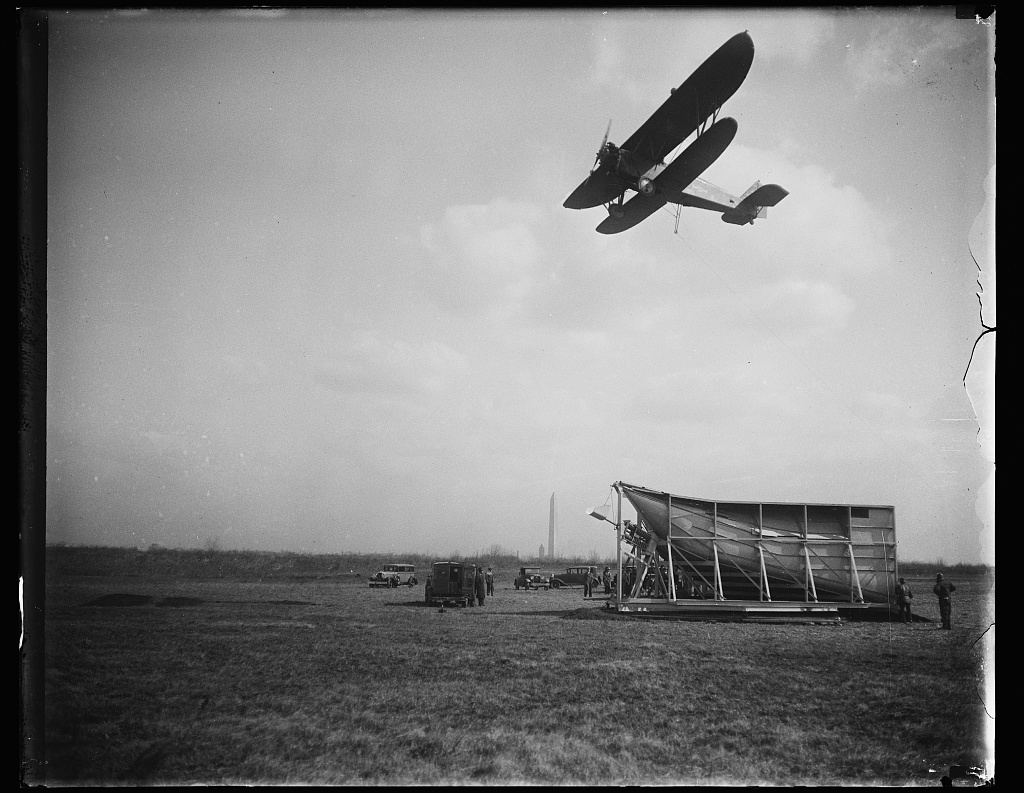 Identified! [Demonstration of a device invented by Dr. Lytle S. Adams that would allow an airplane to pickup airmail, Hoover Field, Arlington, Virginia; Washington Monument in distance]  (LOC)