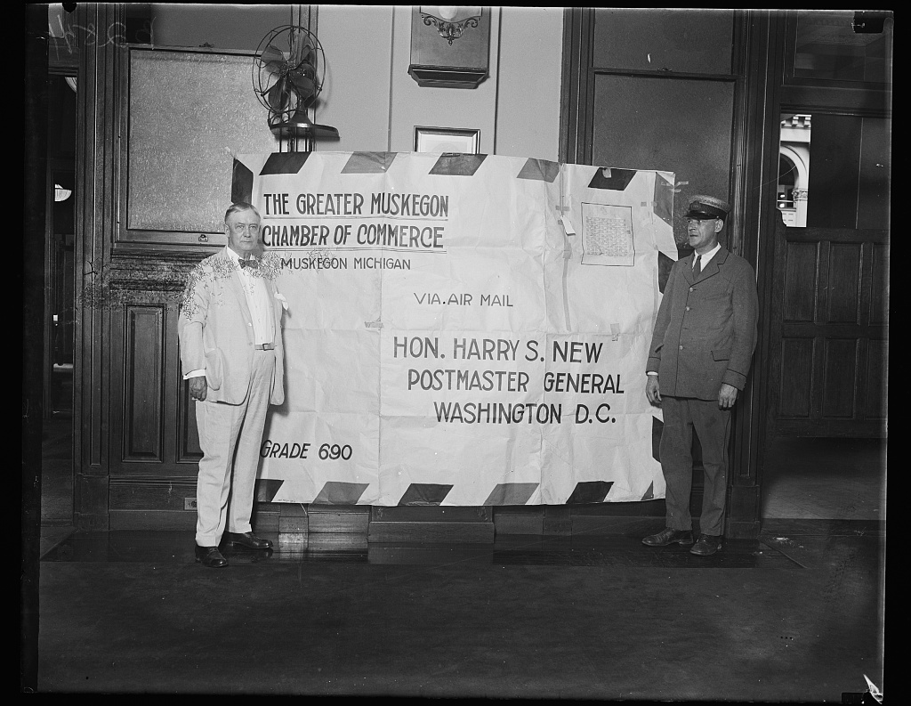 Identified! [Postmaster General Harry S. New, standing next to the largest airmail letter ever sent, from the Greater Muskegon (MI) Chamber of Commerce commemorating the opening of airmail service between Muskegon and Chicago]  (LOC)