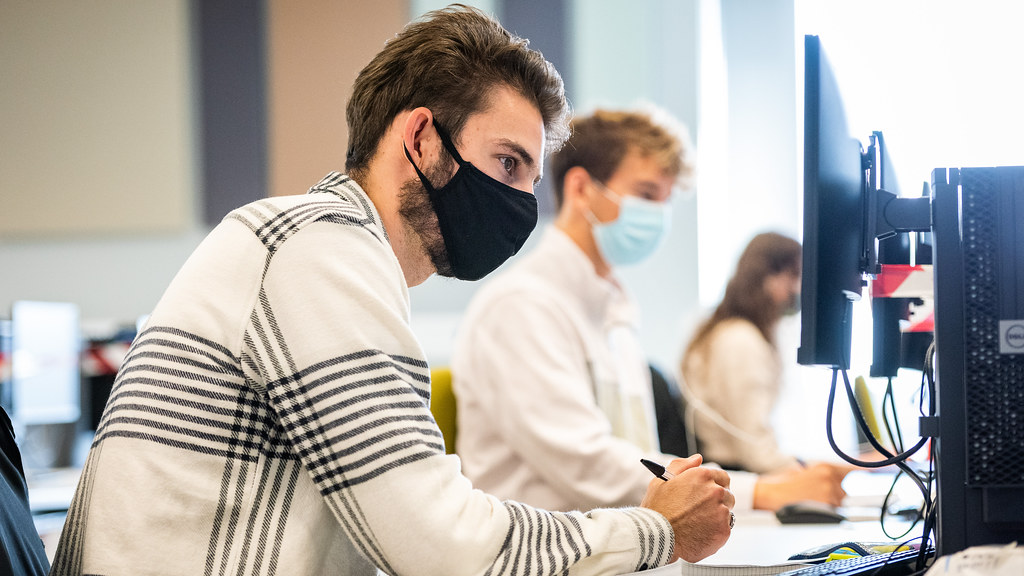 A student wearing a face mask working at a computer on campus.