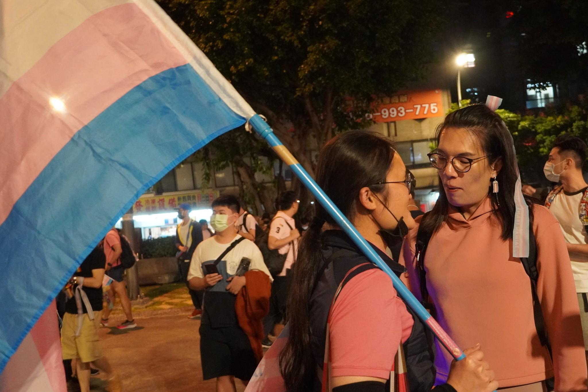 許多人手拿由藍色、粉紅色及白色構成的「跨性別旗」上街。(攝影:張智琦)