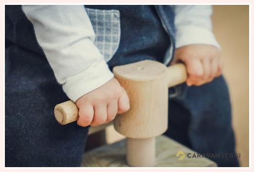 木の自動車に乗る男の子の手のアップ