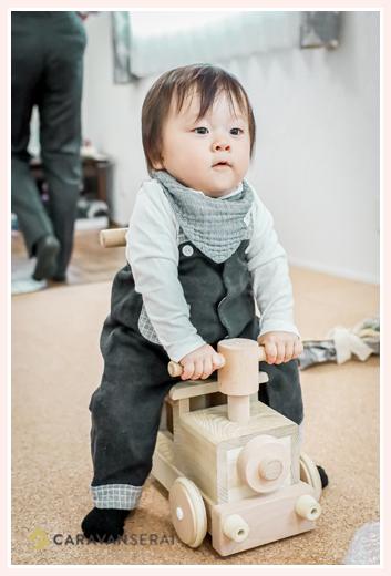木製の機関車おもちゃに乗る男の子