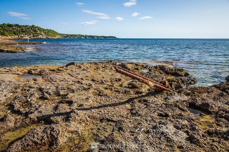 Raíl de vía de tren en las rocas de la playa entre El Molar y Els Bufadors