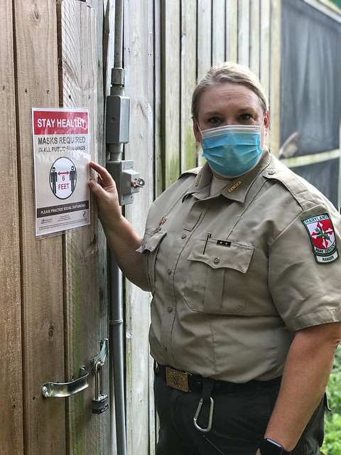 "Photo of ranger with ""masks required"" poster"