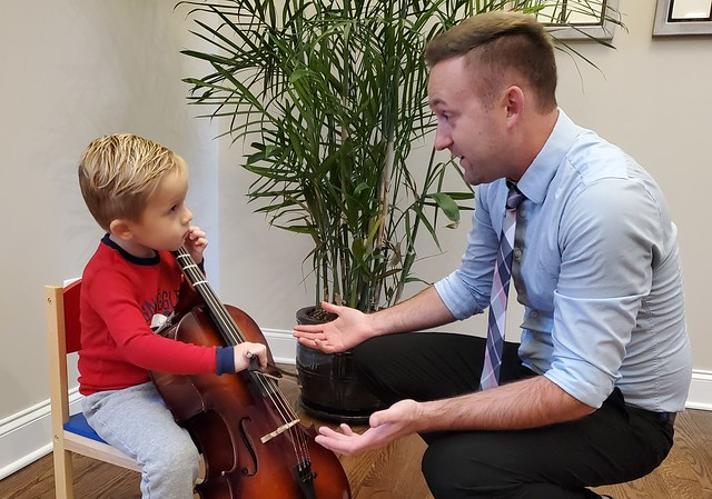Justin Antos with a young cello student.